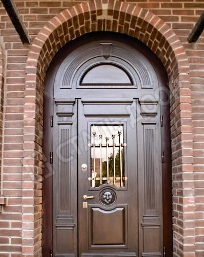 Арочная дверь в коттедж из массива со стеклом и ковкой